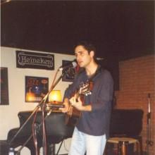 Jorge Drexler cantando y tocando la guitarra en el escenario