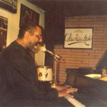Wingfield cantando y tocando el piano
